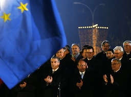 Officials attend the official ceremony of raising the European Union flag in front of Victoria palace, Romania's government headquarters, in Bucharest