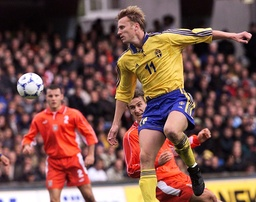 ANDERSSON OF SWEDEN HEADS THE BALL WHILE VKLOS OF POLAND LOOKS ON