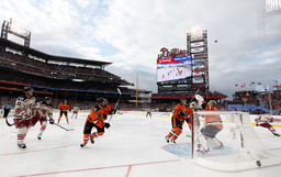 Members of the Philadelphia Flyers and the New York Rangers follow the flying puck during the first period in the NHL Winter Classic hockey game in Philadelphia