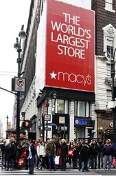 Shoppers cross a street near the Macy's department store in New York