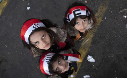 Girls wear headbands in the colours of the Yemen national flag while standing at Taghyeer (Change) Square in Sanaa