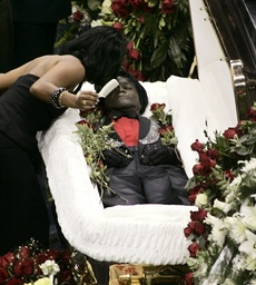James Brown's daughter Deanna Brown leans down to kiss her father's body after fixing his hair during the public funeral at the James Brown Arena in Augusta