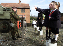 YOUNG GIRLS FROM HOLY CROSS SCHOOL WATCH A BRITISH ARMY PATROL ON THE ARDOYNE ROAD IN BELFAST