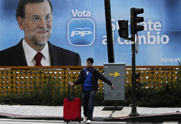 A boy passes in front of election poster of People's Party (Partido Popular) leader Mariano Rajoy on the first day of his electoral campaign in Pontevedra
