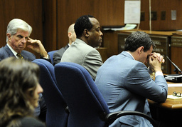 Dr. Conrad Murray listens to deputy District Attorney David Walgren speak in Murray's trial in Los Angeles