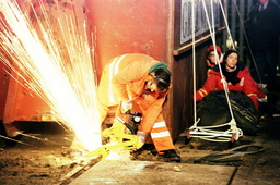 A WORKER CUTS RAILS TO FREE A CONTAINER IN KRUEMMEL