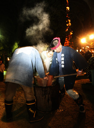 Men in a traditional costumes pound rice into flour to make the Japanese rice cake 'mochi' to celebrate the New Year at the Zojo-ji Buddhist temple in Tokyo