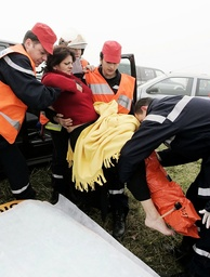 Rescue workers carry injured woman after motorway car crash where some twenty-two people were injured in southwestern France