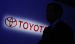 Toyota Motor Corp executive vice president Akio Toyoda walks past a logo of Toyota during a news conference in Tokyo