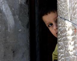A PALESTINIAN BOY LOOKS FROM BEHIND CORNER DURING GUNBATTLES IN BETHLEHEM
