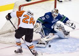 Canucks goalie Cory Schneider stops shot from Philadelphia Flyers Claude Giroux during NHL hockey in Vancouver
