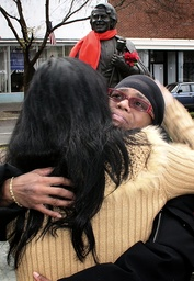 Venisha Brown hugs friend at base of statue of her father, deceased singer James Brown, in his hometown of Augusta