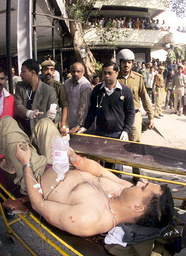 AN INJURED INDIAN POLICE OFFICER LIES ON A STETCHER IN NEW DELHI