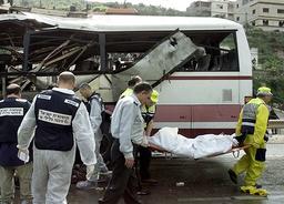 ISRAELI POLICEMEN CARRY A BODY FROM THE WRECKAGE OF A BUS NEAR UMM AL-FAHM