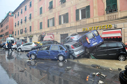 Destroyed cars are seen during a storm in downtown Genoa