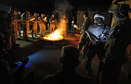 Soldiers with the US Army's 6-4 Cavalry stand around a bonfire and sing Christmas carols at Forward Operating Base Bostick