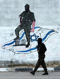 Palestinian gunman walks past mural in Gaza