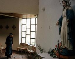 A NUN WALKS INSPECTS DAMAGED CHURCH IN KAKANJ