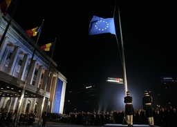 Romanian soldiers raise the European Union flag in front of Victoria palace, Romania's government headquarters, in Bucharest