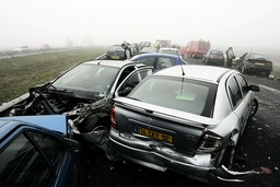 People walk in fog near automobiles after a crash involving more than fifty vehicles where some twenty-two people were injured on French motorway