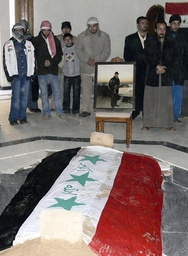 Men stand in front of the grave of Iraq's former president Saddam Hussein during a funeral in Awja, near Tikrit in northern Iraq