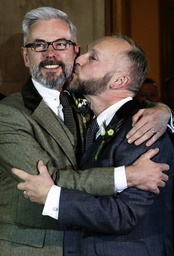 Gay couple Wale and Allard embrace after marrying in the first same-sex wedding in Brighton