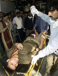 AN INJURED INDIAN POLICE IS STRETCHERED INTO A HOSPITAL IN NEW DELHI
