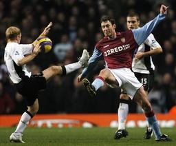Manchester United's Scholes handles the ball as Aston Villa's Sutton challenges during their English Premier League match in Birmingham