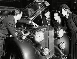 The Motor Show At Earls Court With Salesman Explaining Engine Parts To Potential Customers 1937.