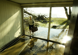 WOMAN LOOKS AT REMNANTS OF STORM DAMAGED HOUSE AFTER HURRICANE ISABEL
