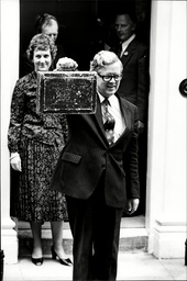 Chancellor Sir Geoffrey Howe Outside No 11 Downing Street With The Budge Box. Lady Howe Is Standing Behind Him.