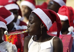 A girl plays with a noise maker while children wait for a presidential speech during a children's Christmas gathering at the national palace in Port-au-Prince
