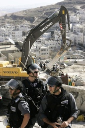 Israeli police officers stand guard as a bulldozer demolishes a Palestinian house in the village of Issawiya