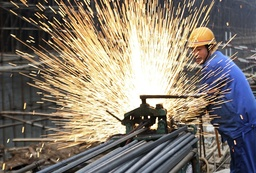 A labourer welds steel bars at a construction site in Huaibei