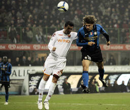 Inter Milan's Crespo jumps to score past AS Roma's Panucci during their Italian Serie A soccer match at the San Siro stadium in Milan