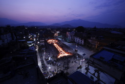 Nepalese people lit candles to create the shape of historic nine-storey Dharara tower and Kasthamandap temple in Kathmandu