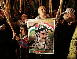 Palestinian women hold a picture of former Iraqi president Saddam during Fatah rally in Gaza