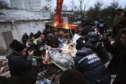 Rescuers carry injured man from debris of shattered five-storey block in Black Sea resort of Yevpatoria in Crimea peninsula