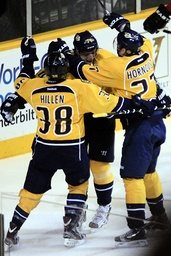 Predators' Kostitsyn celebrates his second goal against Flames with teammates during their NHL hockey game in Nashville