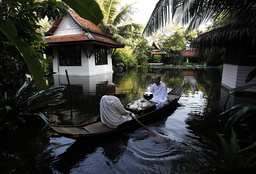 Buddhist nuns travel in a boat through floodwaters after they received food from people at the Sathira-Dhammasathan Buddhist meditation centre in Bangkok