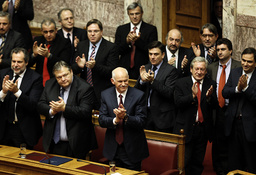 Greek PM George Papandreou and members of his socialist government applaud after winning a vote of confidence in the Greek parliament in Athens
