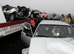 Rescue workers speak to passenger after fifty vehicle pile up due to heavy fog in southwestern France