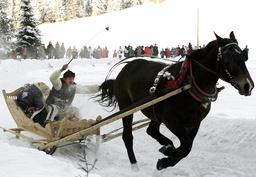 A POLISH HIGHLANDER FLOURISHES A WHIP TO PUSH HIS HORSE