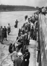Car mechanic with racing cars and spare parts during a training session on the Nuerburgring, 1935