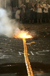 Filipinos watch as firecrackers called 'Judas Belt' are set off to welcome the New Year on a street in Manila