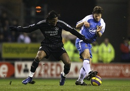 Wigan Athletic's De Zeeuw challenges Chelsea's Drogba for the ball during their English Premier League soccer match in Wigan