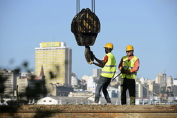 Construction workers build a new bridge against the skyline of Mozambique's capital Maputo