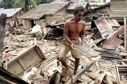 A villager goes through debris in front of his damage house after a flood hit the village of Kota Lintang Bawah