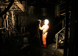 A firefighter searches for bodies of victims inside Santika nightclub in Bangkok