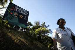 A woman walks near a billboard depicting former Cuban leader Fidel Castro with the headline reading In Santiago, victory always awaits you on the outskirts of Santiago de Cuba